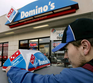 "Photo - FILE - In this Feb. 21, 2007 file photo, Domino's Pizza delivery person Brandon Christensen plugs in the company sign atop his car in Sandy, Utah. The pizza delivery chain on Monday, June 16, 2014 plans to introduce a function on its mobile app that lets customers place orders by speaking with a computer-generated voice named ""Dom.""  (AP Photo/Douglas C. Pizac, File)"