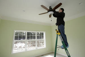 Photo - In this Friday, March 21, 2014 photo, Pete Christman installs a remote control for a fan in a new home in Pepper Pike, Ohio. The National Association of Home Builders reports on sentiment among U.S. builders on Thursday, May 15, 2014. (AP Photo/Tony Dejak)