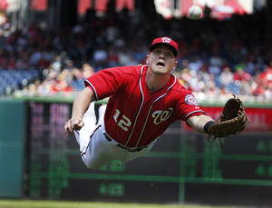 Photo - Washington Nationals first baseman Tyler Moore makes a diving catch for the out on a foul ball hit by New York Mets' Eric Young Jr. during the first inning of a baseball game at Nationals Park Sunday, May 18, 2014, in Washington. (AP Photo/Alex Brandon)