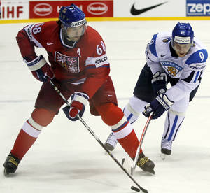 Photo - FILE - In this May 4, 2011, file photo, Czech's Jaromir Jagr, left, challenges for the puck with Finland's Mikko Koivu, from left, during the preliminary round match at the World Hockey Championships in Bratislava, Slovakia. Jagr leads a lively Czech team into his fifth Olympics. (AP Photo/Ronald Zak, File)