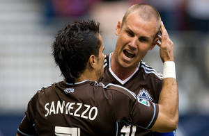 Photo - Vancouver Whitecaps' Camilo Sanvezzo, left, of Brazil, celebrates with Kenny Miller, of Scotland, after scoring a goal against the New England Revolution during the first half of an MLS soccer game in Vancouver, British Columbia, on Saturday June 15, 2013. (AP Photo/The Canadian Press, Darryl Dyck)