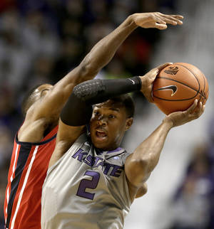 Photo - Kansas State's Marcus Foster (2) looks for a teammate to pass to as he is pressured by Mississippi's Martavious Newby during the first half of an NCAA college basketball game Thursday, Dec. 5, 2013 in Manhattan, Kan. (AP Photo/Charlie Riedel)
