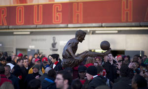 Photo - Fans gather around the statue of former Arsenal player Dennis Bergkamp, in front of the Emirates Stadium, in London, Saturday, Feb. 22, 2014. (AP Photo/Bogdan Maran)