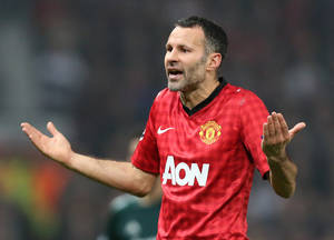 photo - Manchester United&#039;s Ryan Giggs reacts after his teammate Nani was shown a red card during the Champions League round of 16 soccer match against Real Madrid at Old Trafford Stadium, Manchester, England, Tuesday, March 5, 2013. (AP Photo/Jon Super)