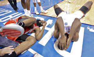 Photo - Houston's James Harden (13) and Oklahoma City's Serge Ibaka (9) react after a collision during Game 2 in the first round of the NBA playoffs between the Oklahoma City Thunder and the Houston Rockets at Chesapeake Energy Arena in Oklahoma City, Wednesday, April 24, 2013. Photo by Chris Landsberger, The Oklahoman