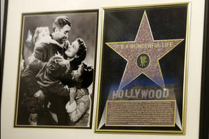 "Photo - In this photo made on Friday, Dec. 20, 2013, a framed plaque with a photograph of a scene from the 1946 film ""It's  A Wonderful Life"" starring Jimmy Stewart, left, and a Hollywood star are on display at the Jimmy Stewart Museum in Indiana, Pa. The museum dedicated to the life of the star of many films including the holiday favorite ""It's A Wonderful Life"" is located in the off-the-beaten track town where Stewart grew up. The museum still attracts visitors from all over the country. It's full of displays not just about Hollywood, but about Stewart's service as a bomber pilot in World War II, his well-to-do ancestors, and his family life. (AP Photo/Keith Srakocic)"