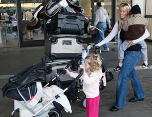 Photo - A traveler with small children makes her way through the Los Angeles International Airport.AP Photo