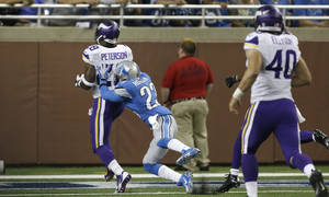 Photo - Detroit Lions cornerback Chris Houston (23) reaches Minnesota Vikings running back Adrian Peterson (28) as he scores a touchdown on the Vikings' first possession of NFL football game in Detroit, Sunday, Sept. 8, 2013. (AP Photo/Carlos Osorio)