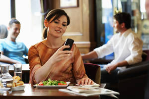 Photo - Woman sitting at table in bar, looking at mobile phone, smiling