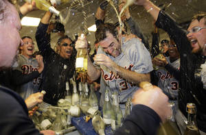 Photo -   Detroit Tigers' Justin Verlander (35) is drenched with sparkling wine by teammates at the end of Game 5 during the American League division baseball series in Oakland, Calif., Thursday, Oct. 11, 2012. (AP Photo/Ben Margot)