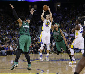 Photo - Golden State Warriors' Stephen Curry (30) makes a three-point basket over Boston Celtics' Jared Sullinger (7) and Jerryd Bayless (11) during the second half of an NBA basketball game on Friday, Jan. 10, 2014, in Oakland, Calif.  Golden State won 99-97. (AP Photo/Marcio Jose Sanchez)