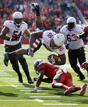 Photo - Temple running back Kenneth Harper (20) dives for yardage over Rutgers defensive back Tejay Johnson (9) during the first half of an NCAA college football game in Piscataway, N.J., Saturday, Nov. 2, 2013. (AP Photo/Mel Evans)