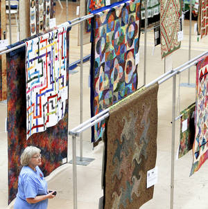 photo - Sherry Massey looks over quilts during the Edmond Quilt Festival at the University of Central Oklahoma.