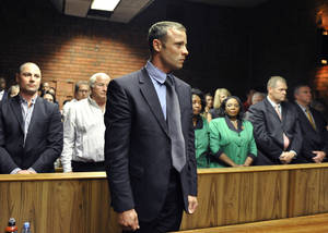 photo - Olympian Oscar Pistorius stands following his bail hearing in Pretoria, South Africa, Tuesday, Feb. 19, 2013. Pistorius fired into the door of a small bathroom where his girlfriend was cowering after a shouting match on Valentine's Day, hitting her three times, a South African prosecutor said Tuesday as he charged the sports icon with premeditated murder. The magistrate ruled that Pistorius faces the harshest bail requirements available in South African law. He did not elaborate before a break was called in the session. (AP Photo)
