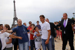 Photo - Spain's Rafael Nadal is escorted by bodyguards after a photo session with his French Open Tennis trophy at Trocadero, next to the Eiffel Tower, in Paris, Monday, June 9, 2014. Rafael Nadal is the French Open champion for the ninth time after successfully defending his title for the fourth straight year. Nadal was a 3-6, 7-5, 6-2, 6-4 winner against second-seed Novak Djokovic. (AP Photo/Francois Mori)
