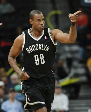 Photo - Brooklyn Nets center Jason Collins acknowledges the cheers from his teammates after Collins hit a basket against the Denver Nuggets late in the fourth quarter of the Nets' 112-89 victory in an NBA basketball game in Denver on Thursday, Feb. 27, 2014. (AP Photo/David Zalubowski)