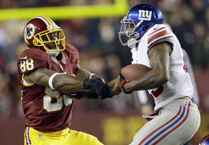 Photo - New York Giants free safety Will Hill, right, takes the football away from Washington Redskins wide receiver Pierre Garcon (88) during the second half of an NFL football game Sunday, Dec. 1, 2013, in Landover, Md. The Giants won 24-17. (AP Photo/Patrick Semansky)