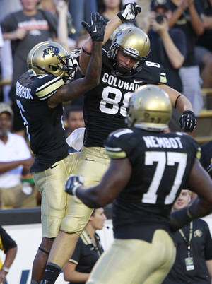 Photo - Colorado wide receiver Paul Richardson, back left, celebrates his touchdown with tight end Kyle Slavin, back right, as offensive lineman Stephane Nimbot, front, looks on against Central Arkansas in the first quarter of a college football game in Boulder, Colo., on Saturday, Sept. 7, 2013. (AP Photo/David Zalubowski)