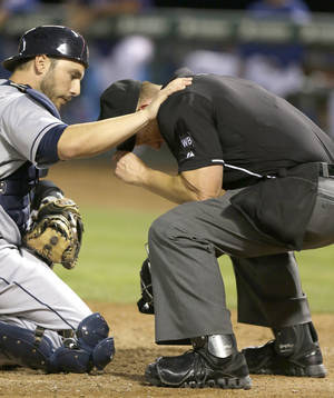 Photo - Cleveland Indians catcher George Kottaras, left, checks on home plate umpire Jim Wolf after Wolf was hit by a pitch during the sixth inning of a baseball game in Arlington, Texas, Monday, June 9, 2014. Wolf left the game. (AP Photo/LM Otero)