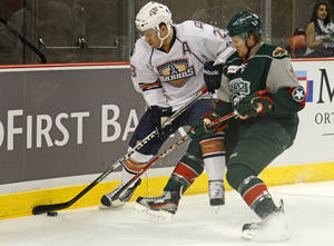 Photo - Ryan Keller of the Oklahoma City Barons tries to control the puck beside Kris Fredheim of the Houston Aeros during an AHL hockey game at the Cox Convention Center in Oklahoma City, Friday, Jan. 27, 2012. Photo by Bryan Terry, The Oklahoman
