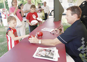 photo - Oklahoma football coach Bob Stoops signs an autograph for a young Sooner fan at the OU Caravan stop Thursday in Tulsa.  Photo by Michael Wayke, Tulsa World