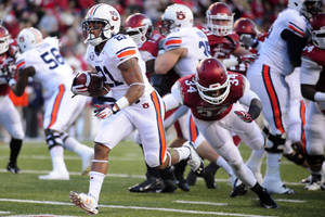 Photo - Auburn running back Tre Mason (21) carries past Arkansas linebacker Braylon Mitchell (34) during the first half of an NCAA college football game in Fayetteville, Ark., Saturday, Nov. 2, 2013. (AP Photo/Beth Hall)