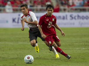 Photo - Liverpool's Philippe Coutinho, left, and Thailand's Chanatip Songkasin vie for the ball during their friendly soccer match at Rajamangala national stadium in Bangkok, Thailand Sunday, July 28, 2013. Liverpool beat Thailand 3-0.(AP Photo/Sakchai Lalit)