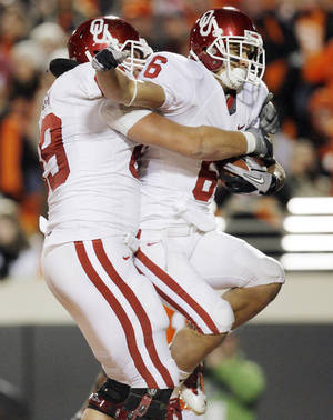 Photo - OU's Eric Mensik (69) celebrates with Cameron Kenney (6) after Kenney caught a touchdown pass in the second quarter during the Bedlam college football game between the University of Oklahoma Sooners (OU) and the Oklahoma State University Cowboys (OSU) at Boone Pickens Stadium in Stillwater, Okla., Saturday, Nov. 27, 2010. Photo by Nate Billings, The Oklahoman