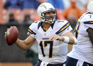 Photo -   As rain falls, San Diego Chargers quarterback Philip Rivers rolls out to pass in the third quarter of an NFL football game against the Cleveland Browns, Sunday, Oct. 28, 2012, in Cleveland. (AP Photo/Phil Long)