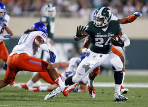 photo -   Michigan State's Le'Veon Bell, right, rushes against Boise State's Jeremy Ioane (10) during the first quarter of an NCAA college football game, Friday, Aug. 31, 2012, in East Lansing, Mich. (AP Photo/Al Goldis)