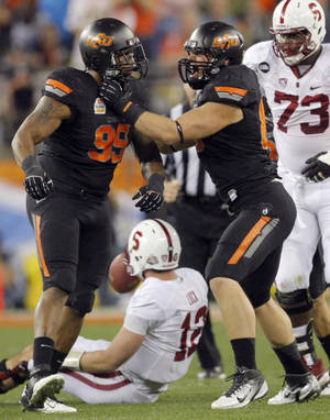 Photo - Oklahoma State's Richetti Jones (99) and Cooper Bassett (80) celebrate Jones' sack on Stanford's Andrew Luck (12) during the Fiesta Bowl between the Oklahoma State University Cowboys (OSU) and the Stanford Cardinal at the University of Phoenix Stadium in Glendale, Ariz., Monday, Jan. 2, 2012. Photo by Sarah Phipps, The Oklahoman