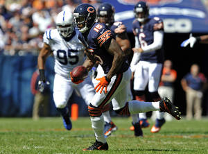 Photo -   Chicago Bears wide receiver Brandon Marshall (15) runs after a reception as Indianapolis Colts defensive end Fili Moala (95) pursues during the first half of an NFL football game in Chicago, Sunday, Sept. 9, 2012. (AP Photo/Jim Prisching)