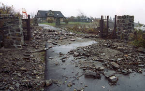 Photo - FILE - In this Nov. 2, 1991 file photo, the driveway leading to U.S. President George H.W. Bush's vacation compound on Walker's Point in Kennebunkport, Maine is littered with rocks and rubble left by 20-foot waves from an Atlantic storm that damaged homes and flooded roads along the coast the previous week. In 2012, Congress passed a law requiring approximately 1.1 million policyholders nationwide to start paying rates based on the true risk of flooding. Thousands of Maine homeowners and businesses could see their flood insurance rise in an attempt to put the troubled National Flood Insurance Program back on sound financial footing. Bush's home is among the properties in the program. (AP Photo/Scott Perry, File)