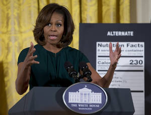 Photo -  First lady Michelle Obama gestures as she speaks Thursday in the East Room of the White House in Washington about helping parents and other consumers make healthier choices as part of her Let's Move program. The Food and Drug Administration is proposing new food labels that would make it easier to know about calories and added sugars, a reflection of the shifting science behind nutrition. AP photo  <strong>Carolyn Kaster -   </strong>