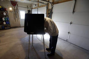 photo -   Bob Warhola casts his vote at a polling place inside a residential garage, Tuesday, Nov. 6, 2012, in Forest City, Pa. After a grinding presidential campaign President Barack Obama and Republican presidential candidate, former Massachusetts Gov. Mitt Romney, yield center stage to American voters Tuesday for an Election Day choice that will frame the contours of government and the nation for years to come. (AP Photo/Matt Slocum)