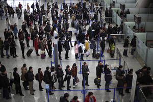 Photo -  Passengers line up for a security check at Pudong International Airport in Shanghai, China.  AP File Photo  <strong>Eugene Hoshiko -   </strong>