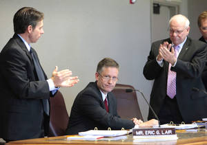 photo - Eric Lair, left, and Gary Ridley applaud Tim Stewart, center, upon being named Oklahoma Turnpike Authority director.