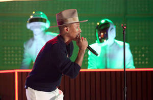 Photo - Pharrell Williams performs with Thomas Bangalter, background left, and Guy-Manuel de Homem-Christo of Daft Punk, at the 56th annual Grammy Awards at Staples Center on Sunday, Jan. 26, 2014, in Los Angeles. (Photo by Matt Sayles/Invision/AP)