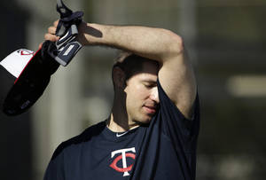 Photo - Minnesota Twins first baseman Joe Mauer wipes his brow during spring training baseball practice Tuesday, Feb. 18, 2014, in Fort Myers, Fla. (AP Photo/Steven Senne)