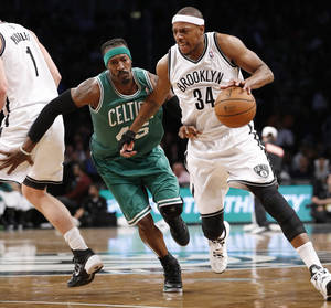 Photo - Brooklyn Nets forward Paul Pierce (34), playing with a protective brace on his injured right hand, drives around Boston Celtics forward Gerald Wallace (45) in the first half of their their NBA basketball game, Tuesday, Dec. 10, 2013, in New York. (AP Photo/Kathy Willens)