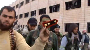 Photo - In this Sunday March 3, 2013 image taken from video obtained from the Shaam News Network, which has been authenticated based on its contents and other AP reporting, a Syrian rebel fighters displays an epaulette from a government soldier during a tour of the police academy complex in Khan al-Asal, in the province of Aleppo, Syria. The Britain-based Syrian Observatory for Human Rights said the rebels seized the police academy in Khan al-Asal after entering the sprawling government complex with captured tanks. The Observatory said the battle left at least 120 soldiers and 80 rebels dead. (AP Photo/Shaam News Network via AP video)
