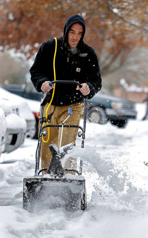 Photo - University of Oklahoma facilities employee Aaron Hanna clears the sidewalks near the dormitories on Friday in Norman.  Photo by Steve Sisney, The Oklahoman <strong>STEVE SISNEY - THE OKLAHOMAN</strong>