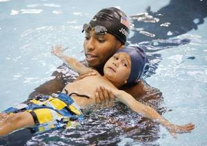 Photo - Olympic gold medalist Cullen Jones works with Charlie Zeeck, 3, on Thursday at the Oklahoma City Community College pool. Jones is touring the country as part of the Make a Splash program, an anti-drowning intiative created by the USA Swimming Foundation. <strong>PAUL HELLSTERN - THE OKLAHOMAN</strong>