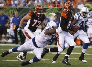 Photo - Cincinnati Bengals quarterback Josh Johnson (8) is pursued by Indianapolis Colts defensive tackle Montori Hughes in the first half of an NFL preseason football game on Thursday, Aug. 29, 2013, in Cincinnati. Colts linebacker Caesar Rayford (49) and Bengals guard Tanner Hawkinson (72) follow. (AP Photo/David Kohl)