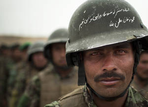 Photo -   In this Wednesday, May 16, 2012 photo, Afghan National Army soldier Mohammed Zaman lines up with other soldiers prior to a patrol in Logar province, eastern Afghanistan. A small love poem to his country is scratched on the surface of his helmet. The Afghan National Army is a critical part of the huge machine being built to protect Afghanistan's security after the NATO alliance is gone in 2014. (AP Photo/Anja Niedringhaus)
