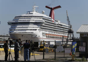 photo - The cruise ship Carnival Triumph is moored at a dock in Mobile, Ala., Friday, Feb. 15, 2013. The ship, which docked Thursday in Mobile after drifting nearly powerless in the Gulf of Mexico for five days, was moved Friday from the cruise terminal to a repair facility. The ship carrying more than 4,200 passengers and crew members had been idled for nearly a week in the Gulf of Mexico following an engine room fire. (AP Photo/Dave Martin)