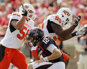 Photo - OSU's Jamie Blatnick (50) and Chris Donaldson (95) celebrate a sack of Texas Tech quarterback Taylor Potts (12) by Donaldson in the first quarter during the college football game between the Oklahoma State University Cowboys and Texas Tech University Red Raiders at Jones AT&T Stadium in Lubbock, Texas, Saturday, October 16, 2010. Photo by Nate Billings, The Oklahoman