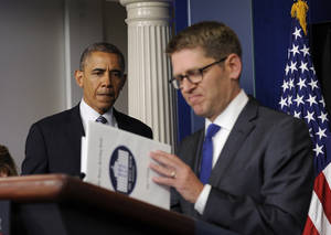 Photo - White House press secretary Jay Carney closes his briefing book as President Barack Obama makes a surprise visit to the Brady Press Briefing Room in Washington, Friday, May 30, 2014, to announces during the daily press briefing that Carney will be stepping down in June. The president announced Carney's departure in a surprise appearance at in the White House press briefing room Friday. He said principal deputy press secretary Josh Earnest will take over the job. (AP Photo/Susan Walsh)