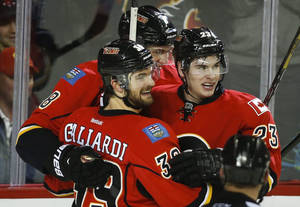 Photo - Calgary Flames' Sean Monahan, right, celebrates his goal with teammate TJ Galiardi during third period NHL hockey action against the San Jose Sharks in Calgary, Canada, Thursday, Jan. 30, 2014. The Flames defeated the Sharks 4-1. (AP Photo/The Canadian Press, Jeff McIntosh)