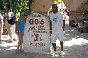 photo - Tourists get their picture taken next to a slab of stone counting down the days until Dec. 21, 2012 at the Xcaret theme park in Playa del Carmen, Mexico, Saturday, Dec. 15, 2012. Amid a worldwide frenzy of advertisers and new-agers preparing for a Maya apocalypse, one group is approaching Dec. 21 with calm and equanimity calm: the people whose ancestors supposedly made the prediction in the first place. Mexico's 800,000 Mayas are not the sinister, secretive, apocalypse-obsessed race they've been made out to be.  (AP Photo/Israel Leal)